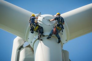 Inspection engineers preparing to rappel down a rotor blade of a wind turbine in a North German wind farm on a clear day with blue sky.